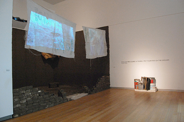Dirt, rocks, fabric, polypropylene sacks, barrow from grandparents from Mexico, slip casted bricks, wood, plastic buckets, video projections, 22 x 12 x …